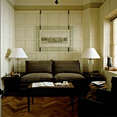 A brown two-seater sofa and table lamps in front of a white wood panelled wall