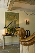 A hallway in a country house with a classical wall table and and mirror