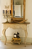 Crystal candelabra an a stripped baroque console table with mirror