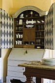 An old fashioned crockery cupboard with a checked pattern inside the doors