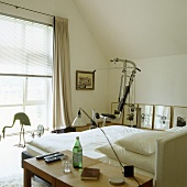 A fitness machine in a simple bedroom with a slopping roof