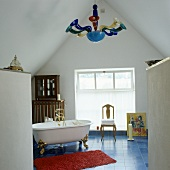 Free standing antique bathtub on blue tile floor in front of a gable wall with a window