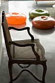An antique chair and colourful rubber cushions on a concrete floor