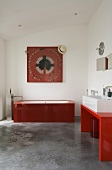 A red glass bathtub in a minimalistic white-painted bathroom with a grey concrete floor