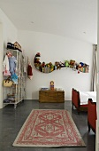 A child's bedroom with a long rug in front of a toy box and a curved wall shelf