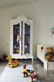 A minimalistic children's bedroom - a child's bike in front of a white-painted antique cupboard