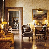 A living room in a palazzo with antique seats bathed in warm artificial light
