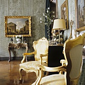 Rococo chairs with gilded frames and a picture hanging above a wall table in a palazzo