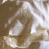 An embroidered piece of fabric with a lace border