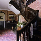 Hallway of a country house with a flight of dark wooden stairs and red-patterned wallpaper