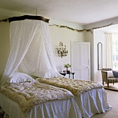 A bedroom in an English country house with a canopy and white bedclothes