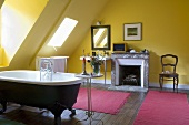 A yellow-painted attic bathroom with a fireplace and pink bathmats in front of an antique, free-standing bathtub