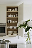 A view of a white crockery in a built-in cupboard with a bunch of flowers on a kitchen counter