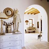 Antiquitäten auf der Kommode mit Blick durch Rundbogen eines Mediterraner Hauses