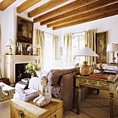 Small items of antique furniture set around a sofa in a comfortable fireplace room with a wood beam ceiling