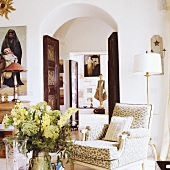 A view through a rounded archway in a Mediterranean house with an upholstered armchair in the anteroom
