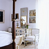 A bedroom with antique, white-painted country house-style furniture