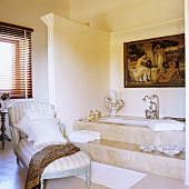 A bathroom with a chaise longue in front of a marble bathtub with steps
