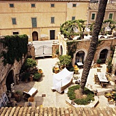 A courtyard of a Mediterranean manor house with terrace furniture and antiques