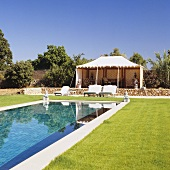 A level pool in a garden with a large gazebo on the terrace