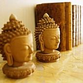 Oriental Buddha heads on a book shelf