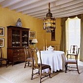 Antique country house furniture with an oriental ceiling lamp in a yellow-painted dining room