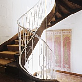 A curved wooden stairway with a white metal banister