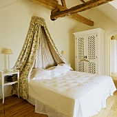 A marital bed with a canopy in a rural bedroom