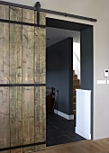 A rustic wooden sliding door from a hallway into a designer apartment