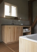 A dignified bathroom - a washstand with a wooden cupboard against a grey wall