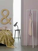 A lamp on a bedside table between a bed and a room divider with a clothes rack