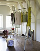 Clothes hanging on a homemade clothes rack in a white-painted attic room