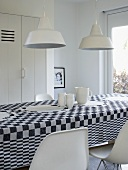 An arrangement of white crockery on a black and white checked tablecloth
