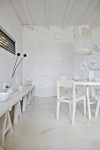 An artistic room design - white containers on a trestle table and a white dining area