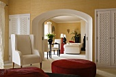 A white armchair and a red upholstered stool in a bedroom with a view through an arched doorway into a living room