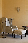 A leather armchair with a footstool and a floor lamp against a gold-papered wall in the corner of a room