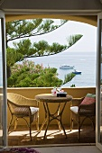Wicker furniture on a balcony with a view of the sea