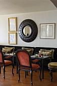 Antike Stühle mit Bistrotisch in Hotelbar und gerahmter Spiegel an der Wand