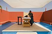 Massage unter Mediterraner Himmel - Frau in Behandlung unter Sonnensegel und Abschirmung mit roter Wand