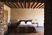 A view of a double bed in a minimalistic bedroom with a wood beam ceiling in a Mediterranean country house