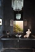 Bad in dunkelgrauer Betonausführung mit gemauertem Waschtisch und Edelstahlbecken vor Fenster und Kronleuchter