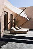 A newly built house in Morocco - loungers on the concrete terrace with a sunshade in front of the window