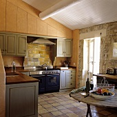 A kitchen in a country house with a natural stone wall