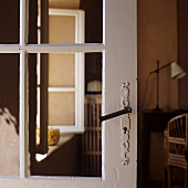 An old glass door with a white wooden frame and a wrought iron handle