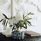 White flowers and olive branches in a vase