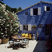Holiday in a blue house - terrace tables and chairs in the sun next to scented oleanders