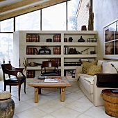 A living room with large windows and a seating corner in front of a stone shelf acting as a room divider