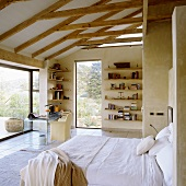 A bed with a view - a shelf on the wall under a wood beam ceiling