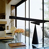 A desk with a glass surface and a black desk lamp in front of a window