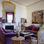 A luxury apartment with purple sofas in front of a fireplace with a Rococo mirror